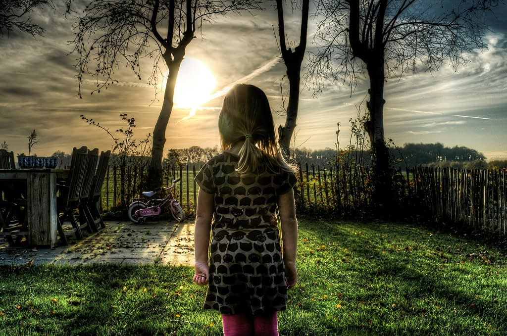 Young girl stands with back to camera looking at the sky image - Skitterphoto on Pixabay