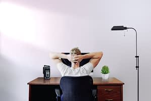 Man leaning back at his home office desk