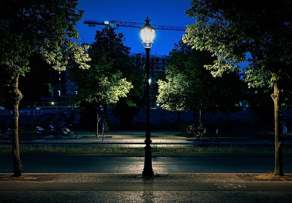 Berlin, Tiergarten. Night photo of a street lamp and green trees in summer