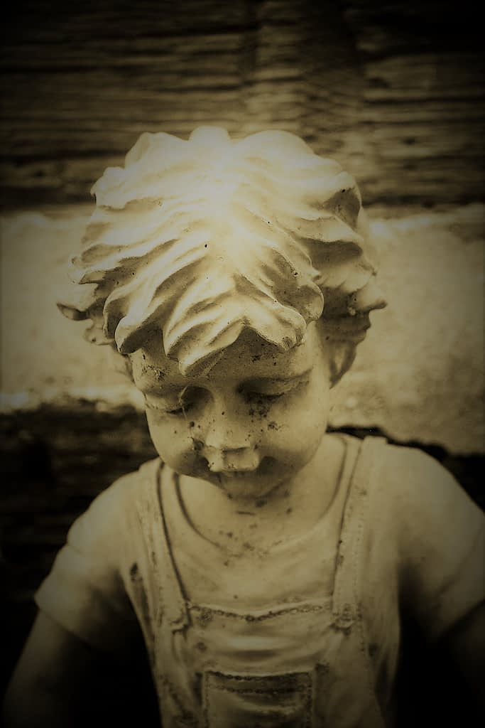 Statue of a boy in a graveyard