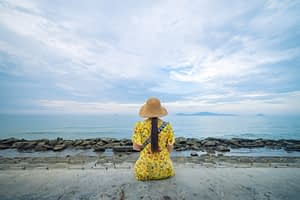 Woman sitting alone on a beach. Yellow dress, back to camera