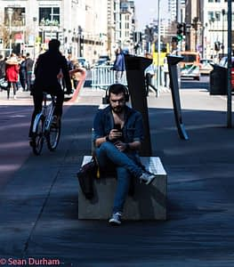 Man sitting alone on a bench in Berlin. Listening to music. Copyright; Sean P. Durham, Berlin 2018
