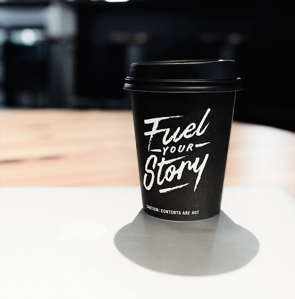 Fuel your Story Copywriting logo on black coffee cup